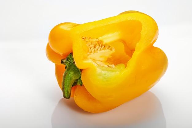 Pimiento amarillo cortado lateralmente, con semillas dentro, sobre un fondo blanco.