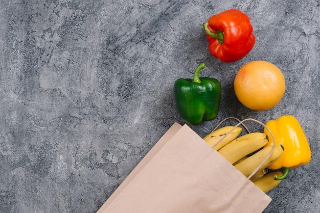 Pimiento colorido; naranja y plátanos sobre fondo gris de hormigón