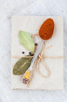 Pimiento picante en la cuchara, laurel y un cuaderno para receta