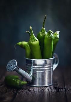 El pimiento picante verde en una regadera esmaltada se toma al estilo de la luna