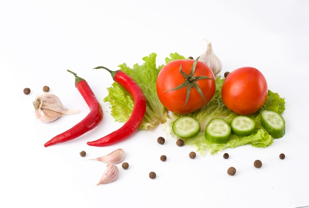Pimiento rojo amargo, pepino y tomate sobre un fondo blanco. verduras frescas sobre un fondo abel.