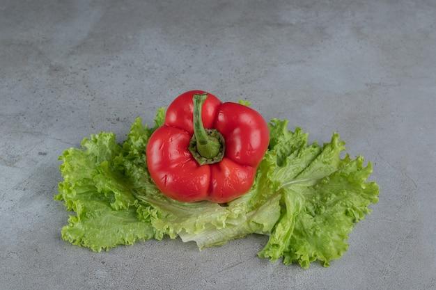 Pimiento rojo fresco con lechuga sobre un fondo gris. foto de alta calidad