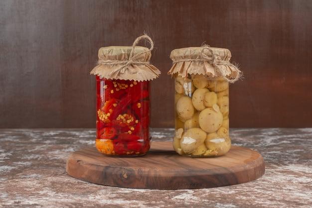 Pimientos y champiñones en escabeche en un frasco de vidrio sobre placa de madera.