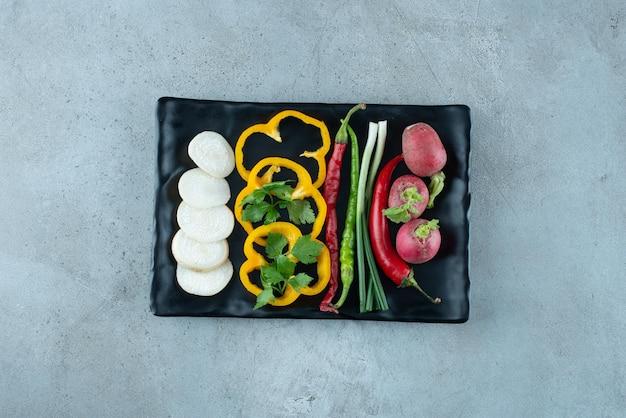Pimientos en rodajas, nabos, verduras y cebollas en un plato negro.