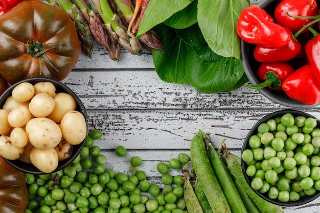 Pimientos rojos con patatas, tomates, espárragos, acedera, vainas verdes, guisantes, zanahorias en un recipiente en la pared de madera, vista desde arriba.