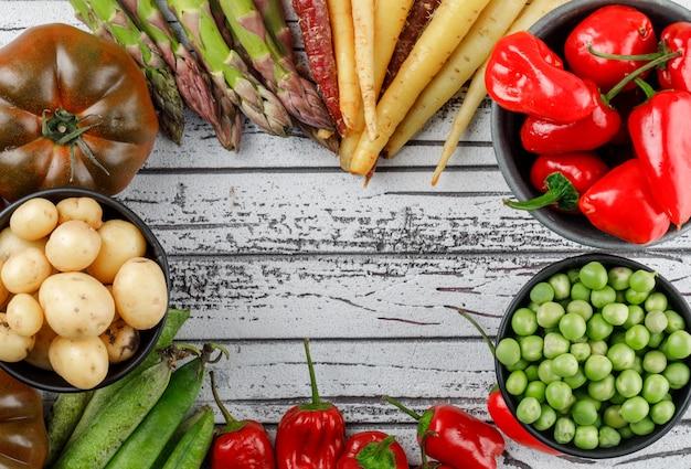 Pimientos rojos con patatas, tomates, espárragos, vainas verdes, guisantes, zanahorias en un recipiente en la pared de madera, vista superior.