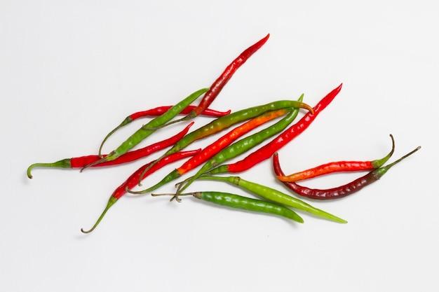 Pimientos rojos y verdes sobre fondo liso