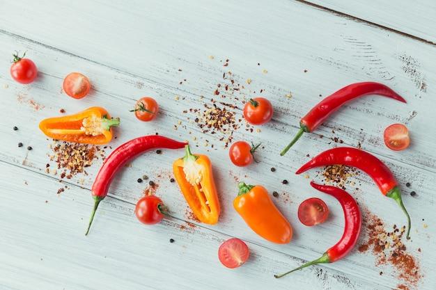 Pimientos surtidos, tomates cherry y especias sobre superficie de madera clara