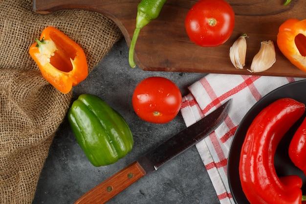 Pimientos, tomates y ajos con un cuchillo alrededor. vista superior.