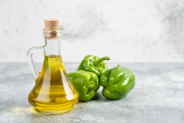 Pimientos verdes con una botella de aceite de oliva virgen extra sobre mesa de mármol.