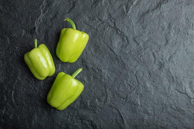 Pimientos verdes frescos sobre negro.