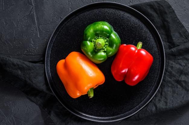 Pimientos verdes, naranjas y rojos en un plato.