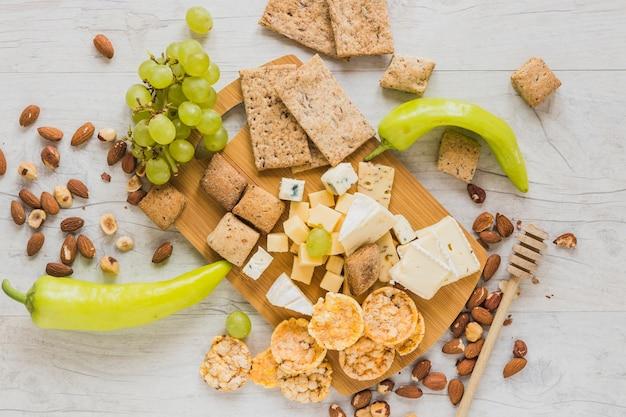 Pimientos verdes, uvas, frutas secas, galletas, pan crujiente y bloques de queso en el escritorio de madera