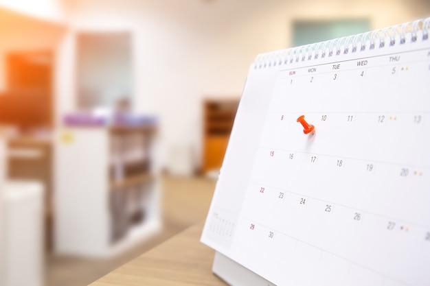 Un pin de color rojo en el calendario en blanco