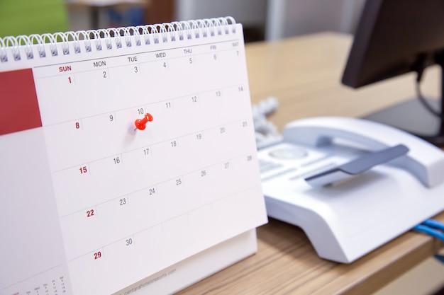 Un pin de color rojo en el concepto de calendario del planificador de eventos.