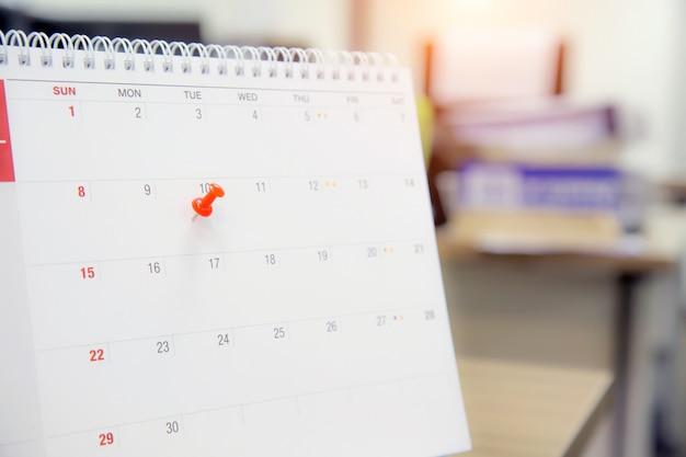 Un pin de color rojo en el concepto de calendario para el planificador de eventos.