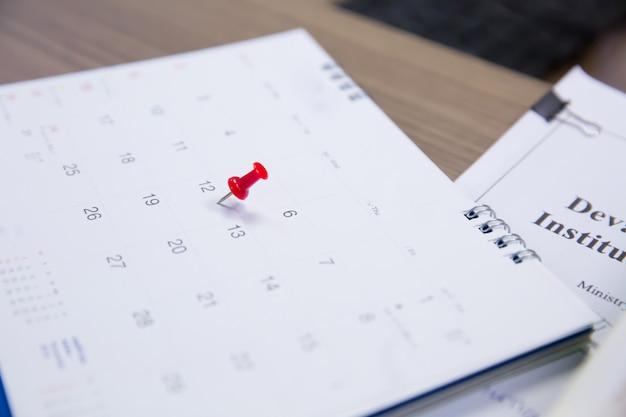 Pin rojo con calendario sobre la mesa.