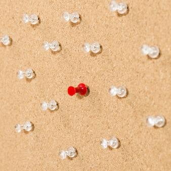 Pin rojo rodeado de pines blancos sobre tabla de madera