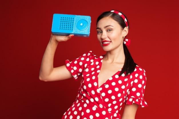 Pin up estilo chica escuchando radio antigua