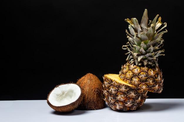 Piña y coco cortados por la mitad en una mesa sobre un negro