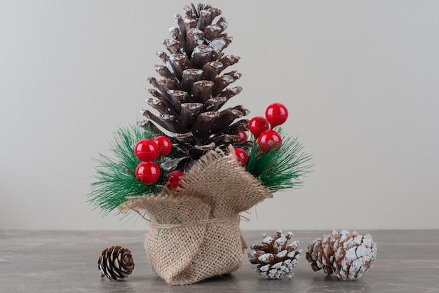 Piña decorada con bayas de acebo y ramas sobre mesa de mármol.
