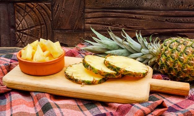 Piña entera y en rodajas en una tabla de cortar y un tazón de arcilla en un azulejo de piedra y tela de picnic. vista lateral.