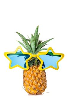 Piña fresca con divertidas gafas de sol amarillas y azules aisladas sobre fondo blanco