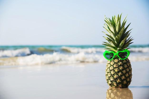 La piña fresca encantadora puso las gafas de sol de la forma del corazón en la playa limpia de la arena con la onda del mar - fruta fresca con concepto de las vacaciones del sol de la arena de mar