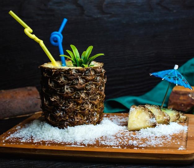 Piña fresca sobre una plancha de madera con coco