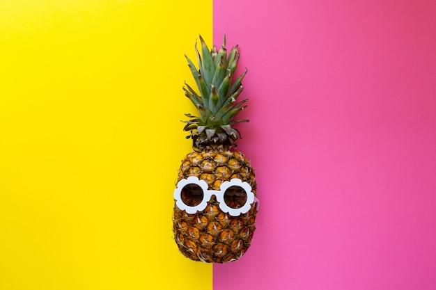 Piña en gafas de sol blancas en el fondo colorido, concepto creativo de verano
