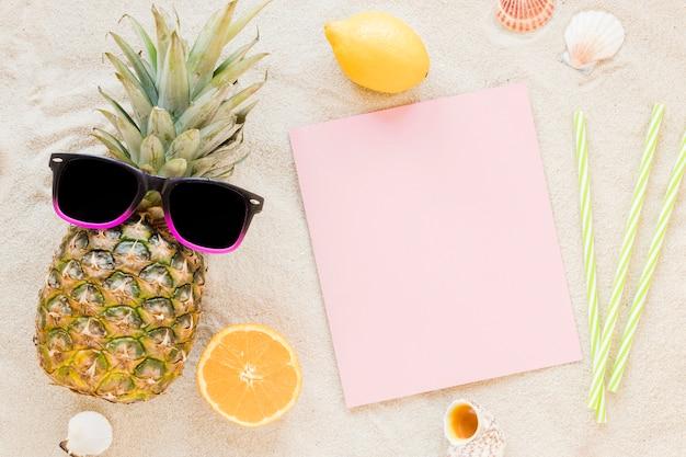 Piña con gafas de sol y papel sobre arena.