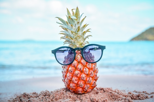 Piña y gafas de sol en la playa st mar verano