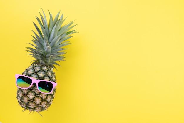Piña con las gafas de sol rosadas para las vacaciones de verano y el concepto de las vacaciones.