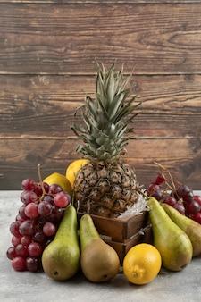 Piña madura en caja de madera con diversas frutas frescas sobre superficie de mármol.