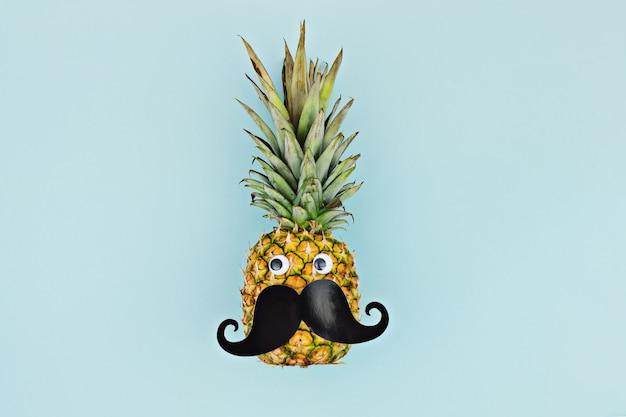 Piña madura de la fruta de la cara divertida con el bigote en fondo azul