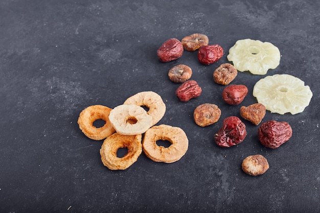 Piña seca, rodajas de manzana y ciruelas sobre fondo gris.