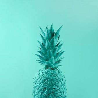Piña turquesa pintada sobre fondo coloreado