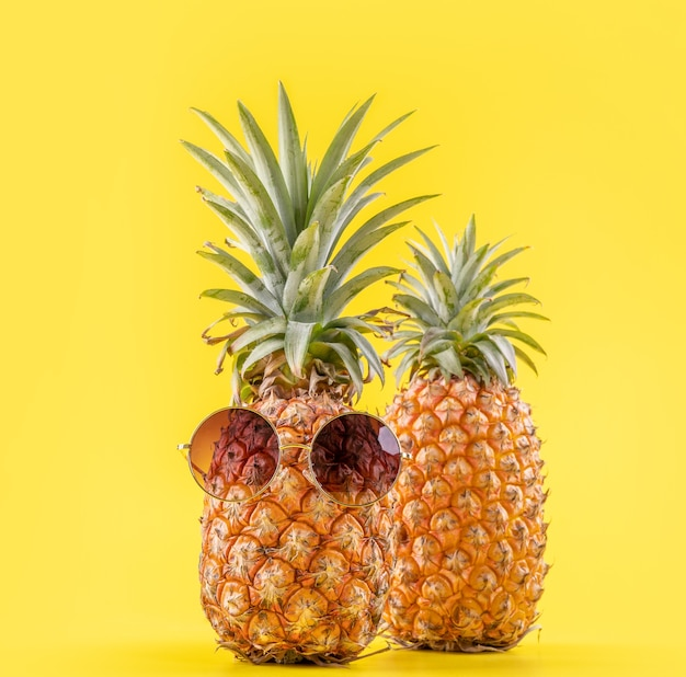Piñas creativas con gafas de sol aisladas sobre fondo amarillo, patrón de diseño de idea de playa de vacaciones de verano, espacio de copia, de cerca, en blanco para texto