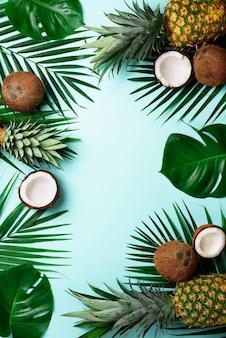 Piñas exóticas, cocos maduros, palmeras tropicales y hojas verdes de monstera.