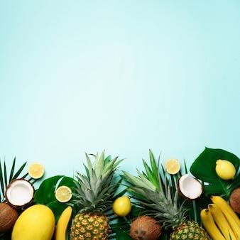 Piñas exóticas, cocos maduros, plátano, melón, limón, palmera tropical y hojas de monstera sobre fondo azul