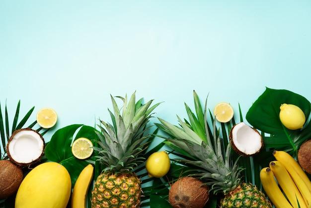 Piñas exóticas, cocos maduros, plátano, melón, limón, palmera tropical y hojas verdes de monstera.