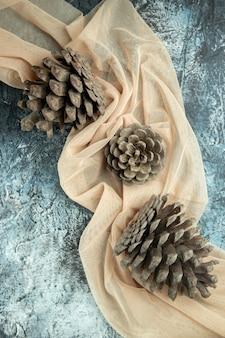 Piñas de vista superior en mantón beige sobre superficie oscura