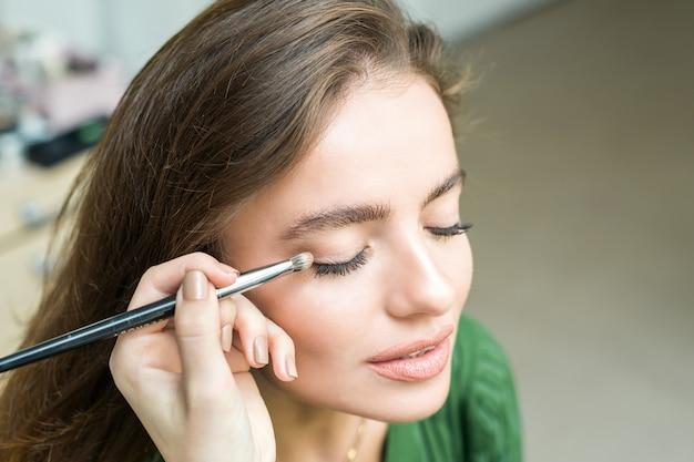 Pincel aplicando maquillaje beige