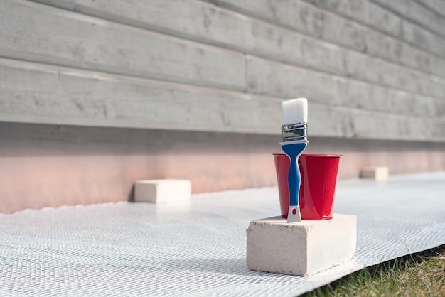 Pincel y balde con pintura junto a la pared exterior de un edificio