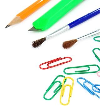 Pincel, clips y lápiz aislado sobre fondo blanco.