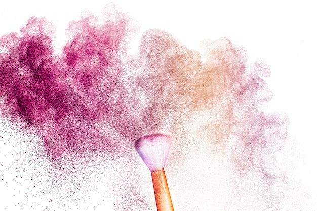 Un pincel dorado con maquillaje en polvo rosado y marrón claro impacta para formar una nube colorida.