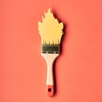 Pincel con llama de papel amarillo sobre color coral