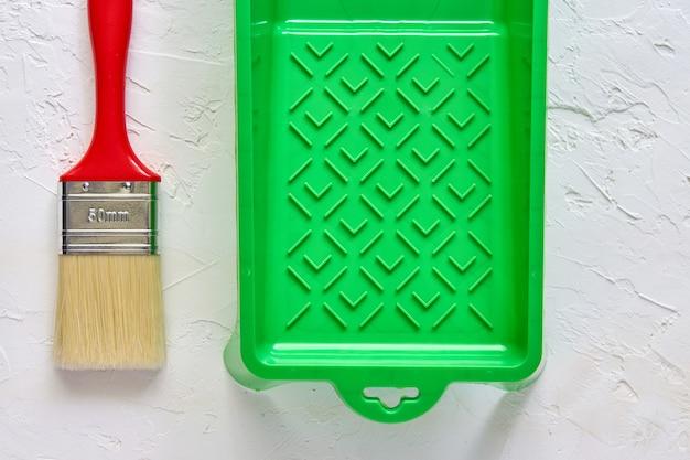 Pincel con mango rojo y bandeja de pintura verde sobre hormigón blanco. herramientas y accesorios para la renovación del hogar. vista superior