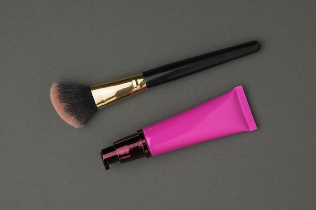 Pincel de maquillaje y crema facial en un tubo rojo sobre una superficie oscura. kit de cuidado facial.