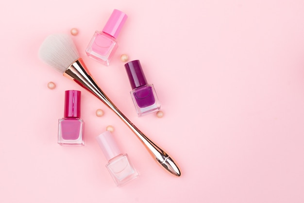 Pincel de maquillaje y esmaltes de uñas sobre un fondo rosa. primer plano con espacio para texto.
